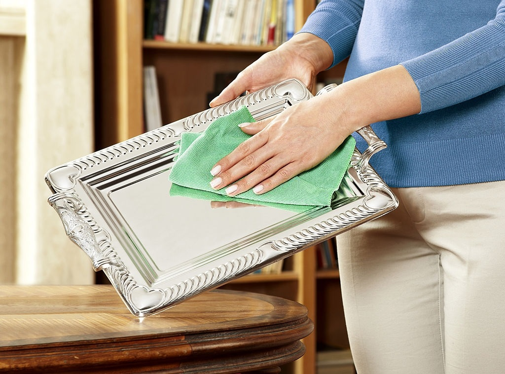 A woman cleaning silver tray