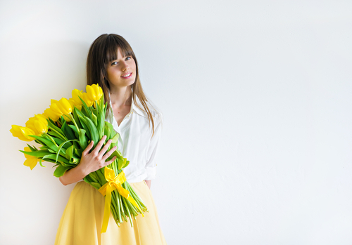 A woman standing with a bouquet of flowers