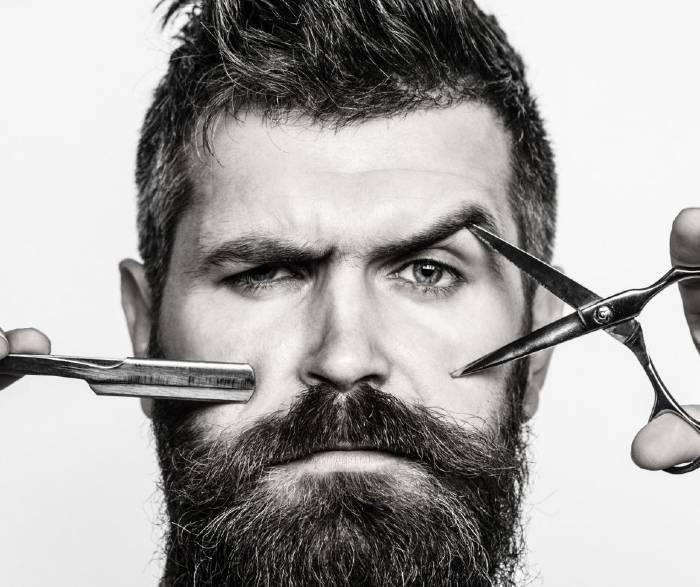 Image of a man having a beard holding scissors and beard cutter