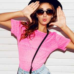 Image of a women wearing shades, a hat and a pink top.