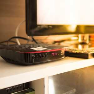Image of a set-top box pl;aced beside a tv