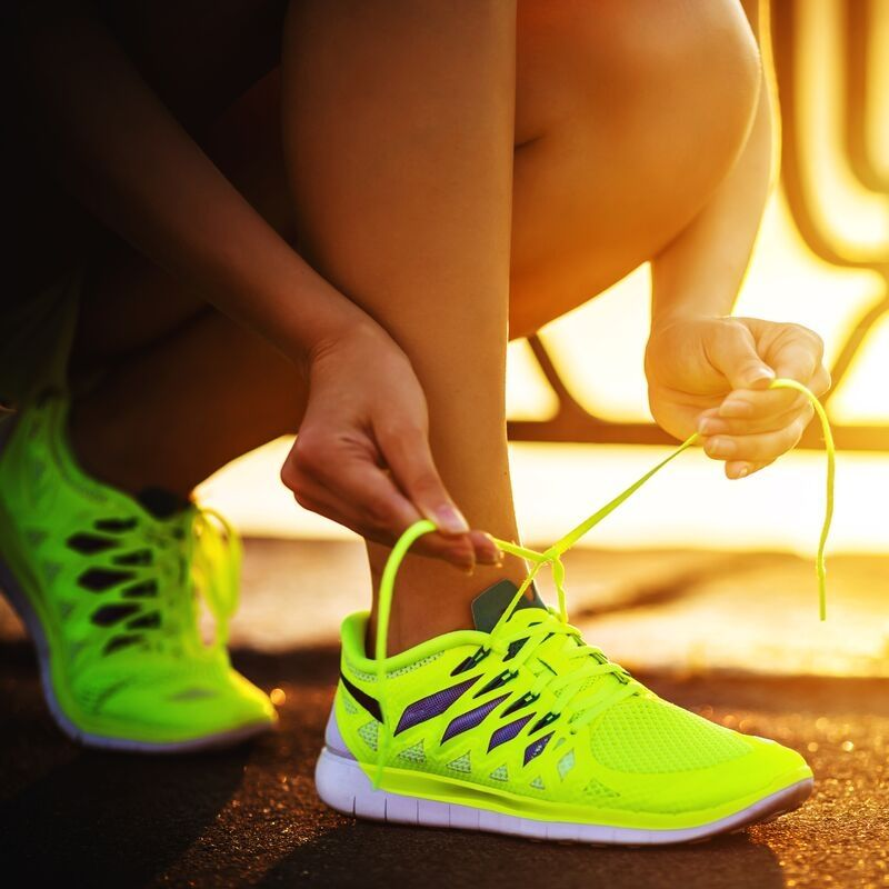 Image of neon shoes where a girl is tieing laces