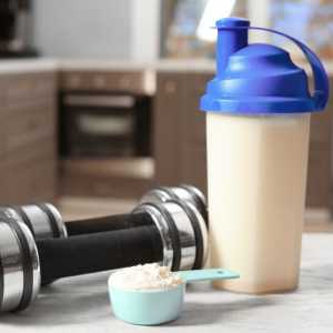 Image of a dumbbell with a scope of mass gainer powder, and a shaker placed at the side.